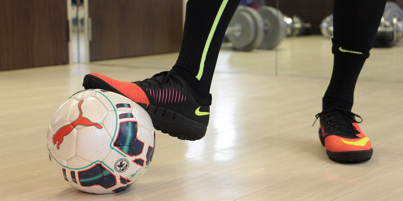 The foot presses the ball